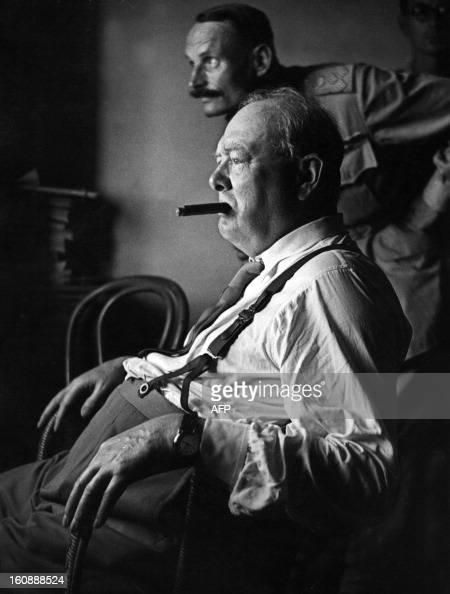 British Prime Minister Sir Winston Churchill stripped to shirt sleeves and smoking a cigar watches an assault against enemy positions north of...