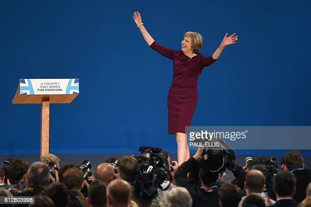 British Prime Minister Theresa gestures as she arrives to deliver a keynote address on the final day of the annual Conservative Party conference at...