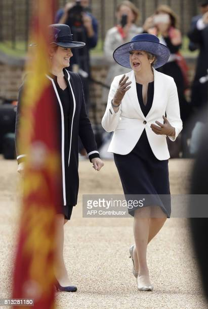 British Prime Minister Theresa May and British Home Secretary Amber Rudd react after Rudd's hat was blown off by the wind as they arrive for a...