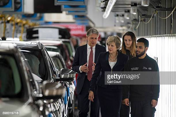 British Prime Minister Theresa May and Chancellor of the Exchequer Philip Hammond talk with staff during a visit to the Jaguar Land Rover factory on...