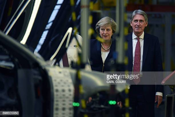 British Prime Minister Theresa May and Chancellor of the Exchequer Philip Hammond view a car production line during a visit to the Jaguar Land Rover...