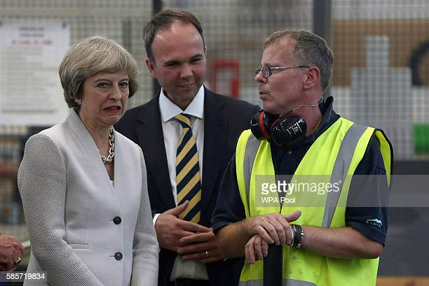 British Prime Minister Theresa May and Croydon Central MP Gavin Barwell speak with a worker as they visit Martinek joinery factory on August 3 2016...