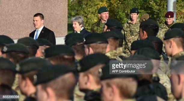 British Prime Minister Theresa May and Estonian Prime Minister Juri Ratas walk past soldiers during a visit at an Estonian military base in Tapa on...