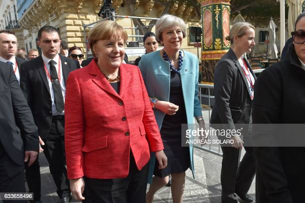 British Prime Minister Theresa May and Germany's Chancellor Angela Merkel arrive to pose for a family picture during an European Union summit on...