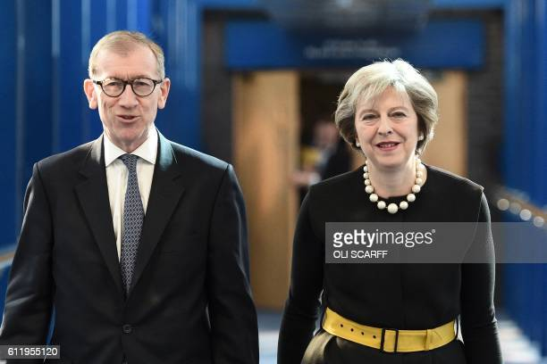 British Prime Minister Theresa May and her husband Philip John May walk along the bridge from the hotel to the International Convention Centre in...