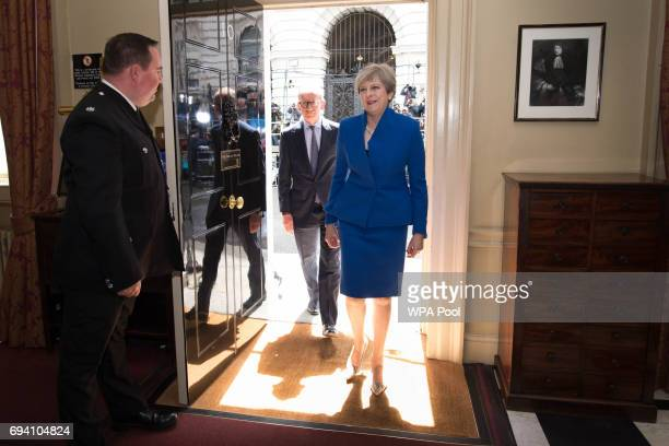 British Prime Minister Theresa May and her husband Philip walk into into 10 Downing Street after returning from seeing Queen Elizabeth II at...