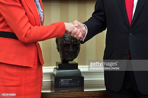 British Prime Minister Theresa May and US President Donald Trump shake hands beside a bust of former British Prime Minister Winston Churchill in the...
