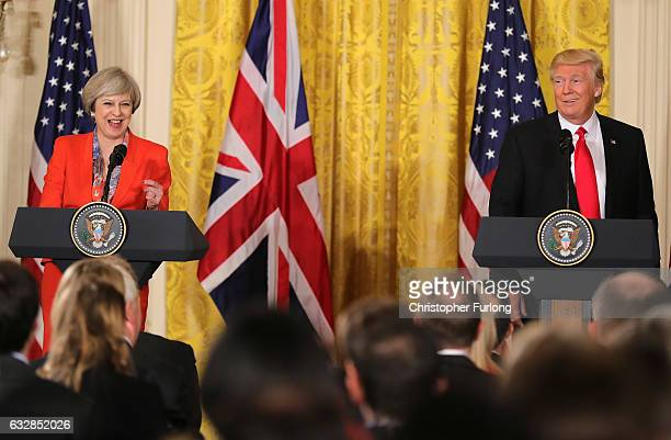 British Prime Minister Theresa May and US President Donald Trump smile during a joint press conference in The East Room at The White House on January...