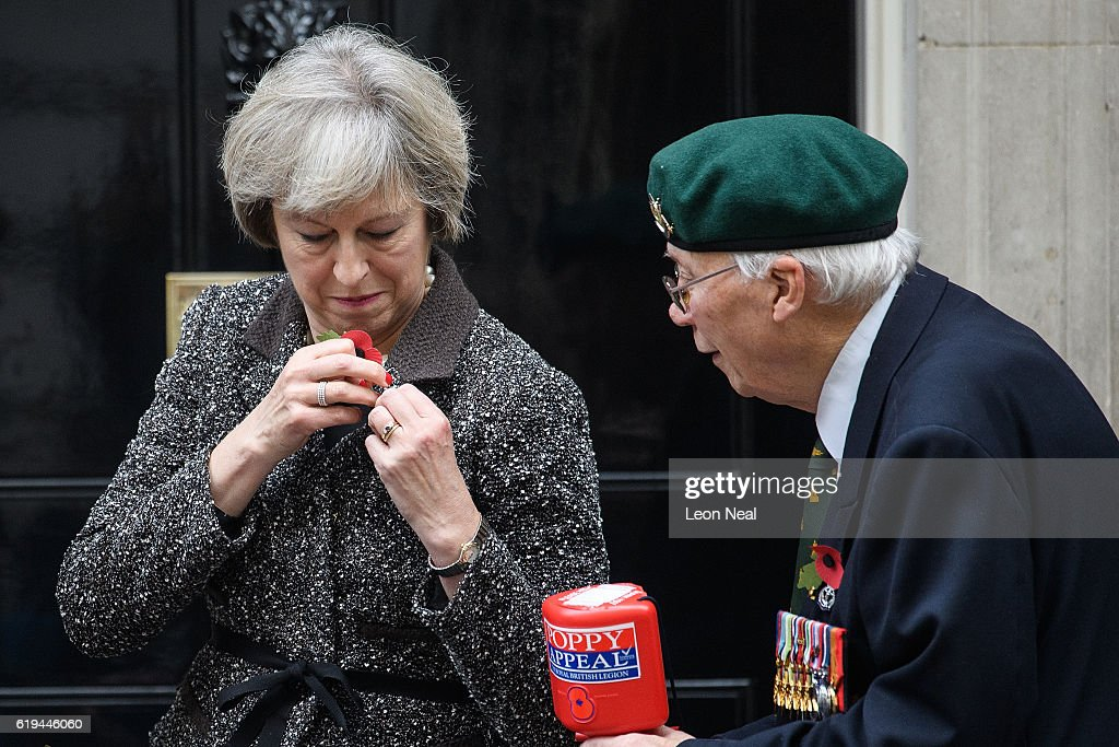 British Prime Minister Theresa May (L) attaches her poppy as she takes part in a photocall for this years 'Poppy Appeal' with veteran Roy Miller (R) at Downing Street on October 31, 2016 in London, England. This year, The Royal British Legion is asking the nation to 'Rethink Remembrance' by recognising the sacrifices made not just by the Armed Forces of the past, but by today's generation too.