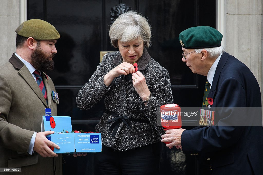 British Prime Minister Theresa May (C) attaches her poppy as they take part in a photocall for this years 'Poppy Appeal' with veterans Stewart Harris (L) and Roy Miller (R) at Downing Street on October 31, 2016 in London, England. This year, The Royal British Legion is asking the nation to 'Rethink Remembrance' by recognising the sacrifices made not just by the Armed Forces of the past, but by today's generation too.