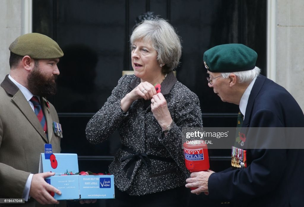 British Prime Minister Theresa May (C) attaches her remembrance poppy during a photo call with British veterans Roy Miller (R), 92, and Stewart Harris (L), 32, after the prime minister made a donation to the Royal British Legion's Poppy Appeal in Downing Street, central London on October 31, 2016. In the run up to Remembrance Sunday, a commemoration of the contribution of British and Commonwealth servicepeople in the two World Wars and later conflicts, The Royal British Legion distributes remembrance poppys in return for donations to their 'Poppy Appeal', which supports all current and former British military personnel. / AFP / Daniel Leal-Olivas