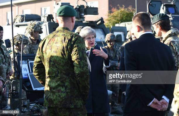 British Prime Minister Theresa May French President Emmanuel Macron and Estonian Prime Minister Juri Ratas talk to soldiers during a visit at an...