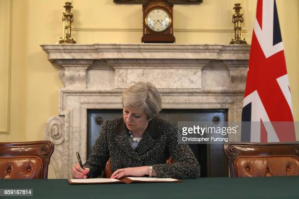 British Prime Minister Theresa May in the cabinet office signs the official letter to European Council President Donald Tusk invoking Article 50 and...