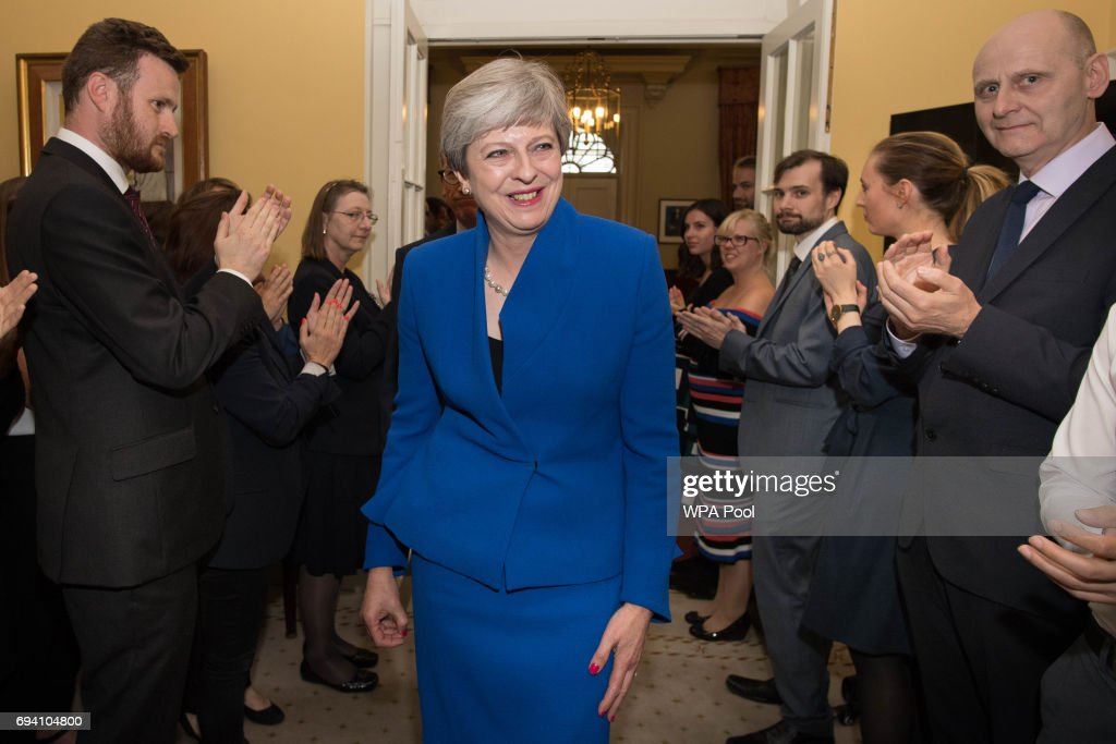 British Prime Minister Theresa May is clapped into 10 Downing Street in by staff after returning from seeing Queen Elizabeth II at Buckingham Palace on June 9, 2017 in London, United Kingdom. After a snap election was called by Prime Minister Theresa May the United Kingdom went to the polls yesterday. The closely fought election has failed to return a clear overall majority winner and Theresa May has formed a minority Government with the support of Northern Ireland's Democratic Unionist Party.
