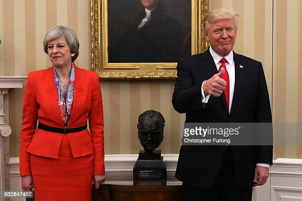 British Prime Minister Theresa May looks on as US President Donald Trump gives the thumbs up in The Oval Office at The White House on January 27 2017...
