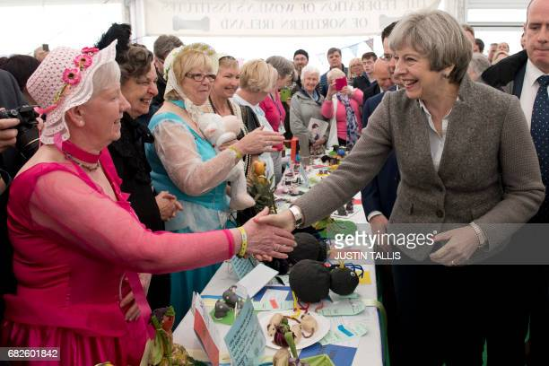 British Prime Minister Theresa May meets members of the women's institute at the Balmoral Show near Lisburn Northern Ireland on May 13 2107 during a...
