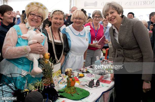 British Prime Minister Theresa May poses for a photograph with members of the women's institute at the Balmoral Show near Lisburn Northern Ireland on...