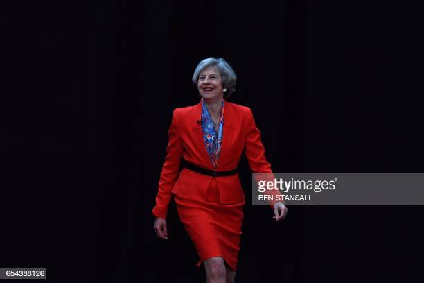 British Prime Minister Theresa May reacts as she arrives on stage to deliver her address to delegates at the Conservative Party Spring Conference in...