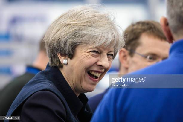 British Prime Minister Theresa May shares a laugh with a worker as she tours the UTC Aerospace Systems factory during a campaign visit on May 6 2017...
