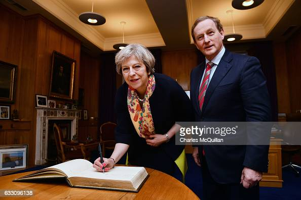 British Prime Minister Theresa May signs the visitors book watched by Irish Taoiseach Enda Kenny at Government Buildings on January 30 2017 in Dublin...