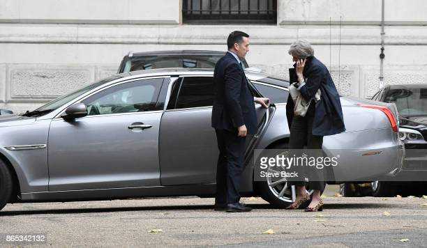 British Prime Minister Theresa May speaks on her mobile phone as she arrives for work at the rear entrance of 10 Downing Street on October 23 2017 in...