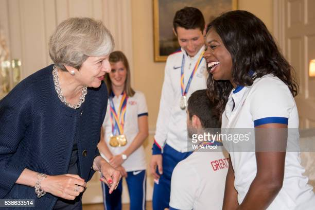 British Prime Minister Theresa May speaks to Asha Philip who won silver in the 4x100m during a a reception for who competed in the World Athletics...