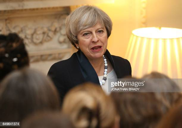 British Prime Minister Theresa May speaks to guests during an International Women's Day reception at 10 Downing Street in London on March 8 2017 /...