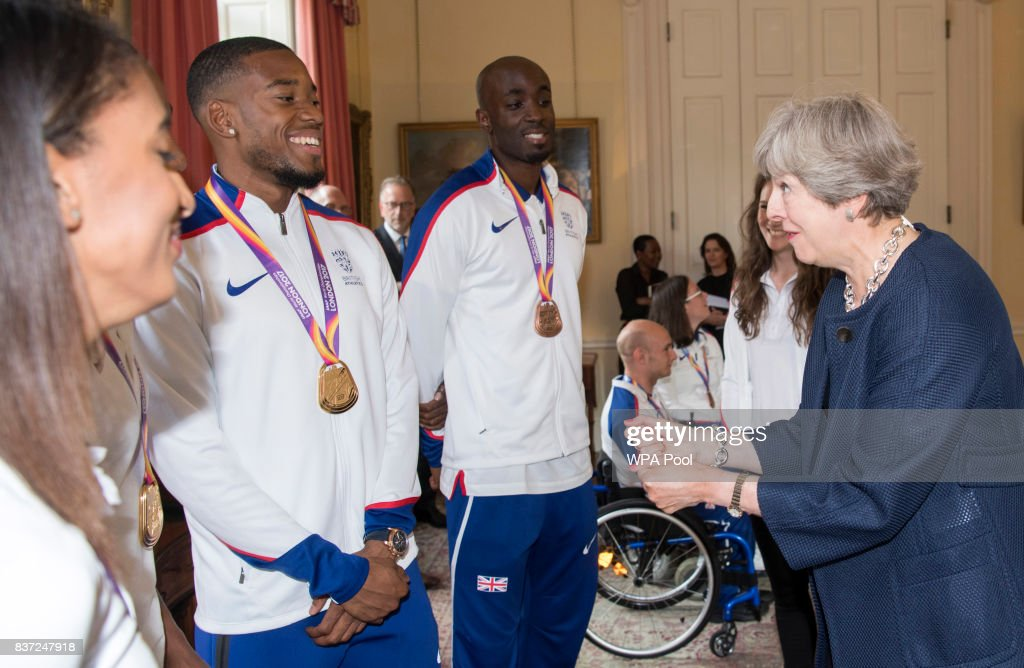 British Prime Minister Theresa May speaks to Nethaneel Mitchell-Blake and Dwayne Cowan during a reception for who competed in the World Athletics Championships and World Para Athletics at 10 Downing Street on August 22, 2017 in London, England.