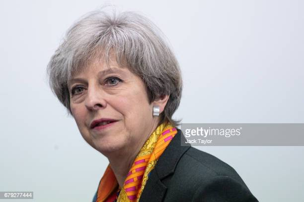 British Prime Minister Theresa May speaks to workers as she tours the Octink sign manufacturers' factory with local prospective Conservative...