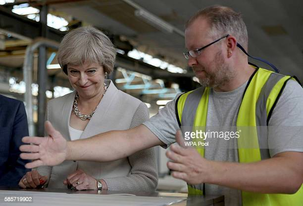 British Prime Minister Theresa May speaks with a worker as she visits Martinek joinery factory on August 3 2016 in London United Kingdom