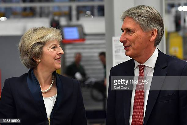 British Prime Minister Theresa May speaks with Chancellor of the Exchequer Philip Hammond during a visit to the Jaguar Land Rover factory on...