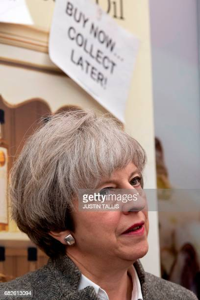 British Prime Minister Theresa May speaks with stall holders as she walks around at the Balmoral Show near Lisburn Northern Ireland on May 13 2107...