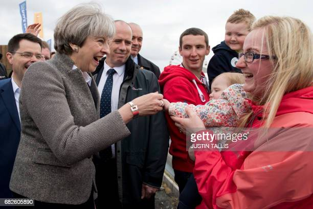 British Prime Minister Theresa May speaks with visitors as she walks around outside at the Balmoral Show near Lisburn Northern Ireland on May 13 2107...