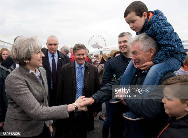 British Prime Minister Theresa May speaks with visitors as she walks around at the Balmoral Show near Lisburn Northern Ireland on May 13 2107 during...