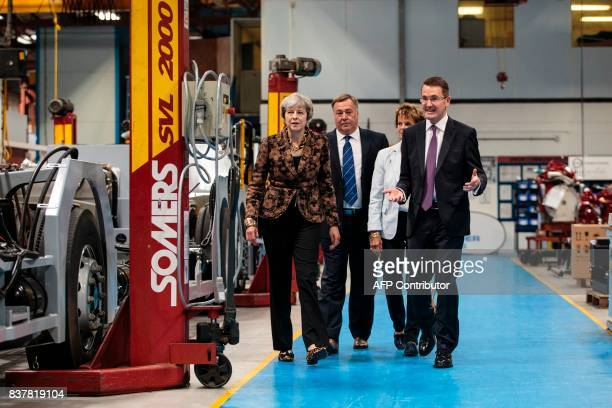 British Prime Minister Theresa May staff as she tours the Alexander Dennis bus and coach manufacturers factory in Guildford south of London on August...