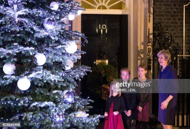British Prime Minister Theresa May stands with children who won the annual Christmas card competition during the switch on of the Christmas tree...