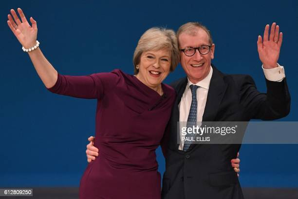 British Prime Minister Theresa May stands with her husband Philip John May as they wave to delegates following her keynote address on the final day...