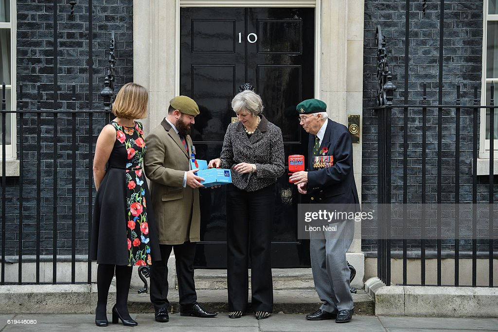 British Prime Minister Theresa May (2R) takes part in a photocall for this years 'Poppy Appeal' with British Legion Director of Communications Claire Rowcliffe (L) and veterans Stewart Harris (2L), Roy Miller (R) at Downing Street on October 31, 2016 in London, England. This year, The Royal British Legion is asking the nation to 'Rethink Remembrance' by recognising the sacrifices made not just by the Armed Forces of the past, but by today's generation too.