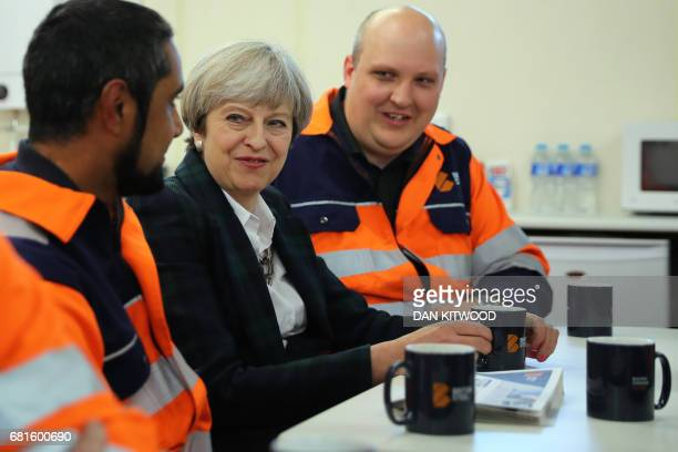 British Prime Minister Theresa May talks to staff in a tea room at British Steel in Scunthorpe northern England on May 10 as campaigning continues in...