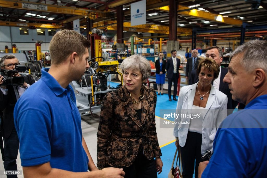 British Prime Minister Theresa May (C) talks with workers as she tours the Alexander Dennis bus and coach manufacturers factory in Guildford, south of London, on August 23, 2017. The company has secured a 44-million GBP government finance deal to sell Britain's famous red double-decker buses to Mexico. A £1.7 billion package of taxpayer-funded support to help businesses make the most of opportunities outside of the European Union has helped 137 firms expand and win overseas contracts over the past year, the prime minister said. / AFP PHOTO / POOL / Jack Taylor