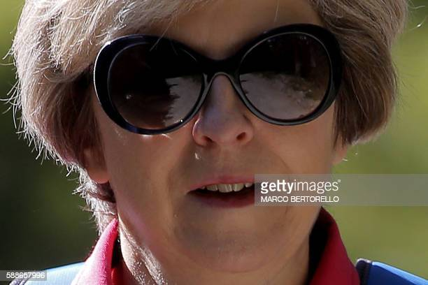 British Prime Minister Theresa May walks in a forest at the start of a summer holiday in the Alps in Switzerland on August 12 2016 with her husband...