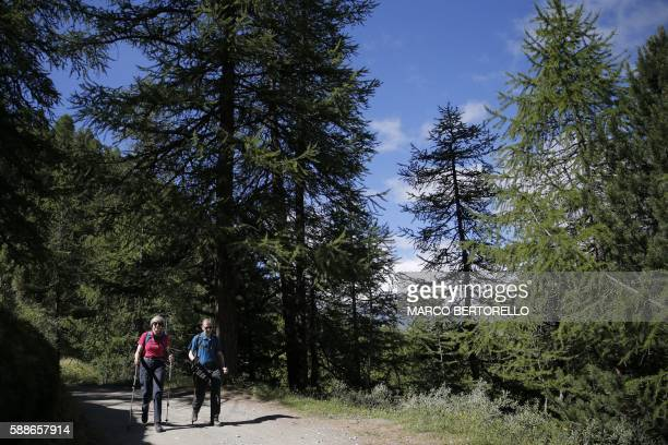 British Prime Minister Theresa May walks in a forest with her husband Philip at the start of a summer holiday in the Alps in Switzerland on August 12...