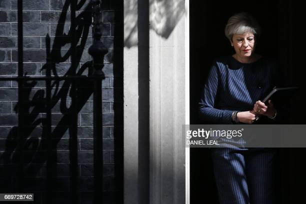 TOPSHOT British Prime Minister Theresa May walks out of 10 Downing Street to speak to media in central London on April 18 2017 British Prime Minister...