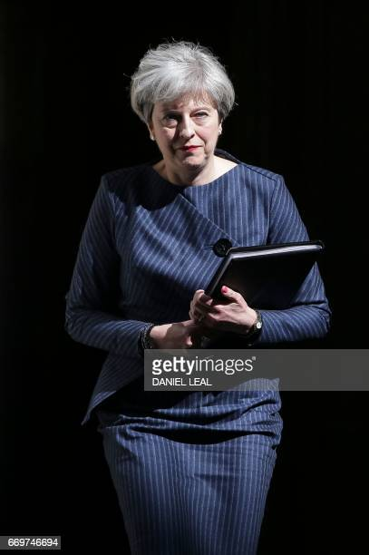 British Prime Minister Theresa May walks out of 10 Downing Street to make a statement to the media in central London on April 18 2017 British Prime...