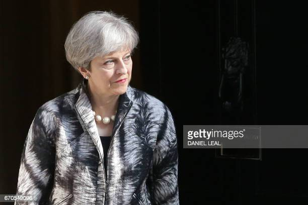 British Prime Minister Theresa May walks out of 10 Downing street to greet European Parliament President Antonio Tajani in central London on April 20...