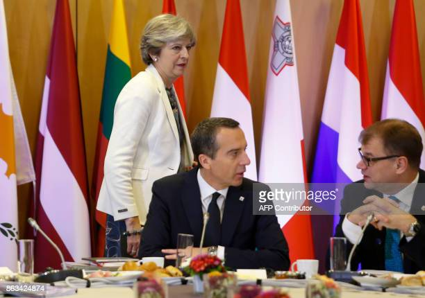 British Prime Minister Theresa May walks past Austria's Chancellor Christian Kern and Finland's Prime Minister Juha Sipila arrives on the second day...