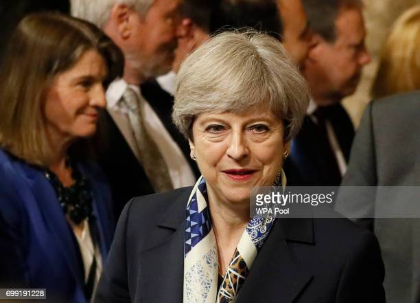 British Prime Minister Theresa May walks through the House of Commons to attend the the State Opening of Parliament taking place in the House of...
