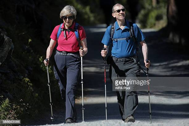 British Prime Minister Theresa May walks with her husband Philip John May while on summer holiday on August 12 2016 in the Alps of Switzerland The...