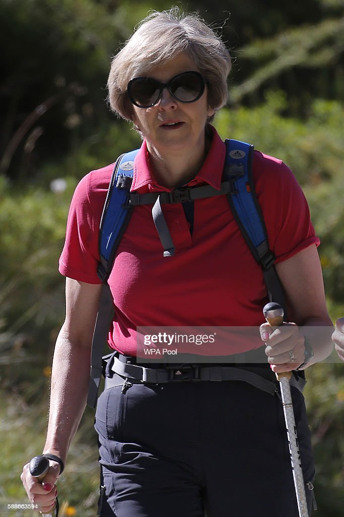 British Prime Minister Theresa May walks with her husband Philip John May while on summer holiday on August 12, 2016 in the Alps of Switzerland. The Prime Minister is due back to work on August 24.
