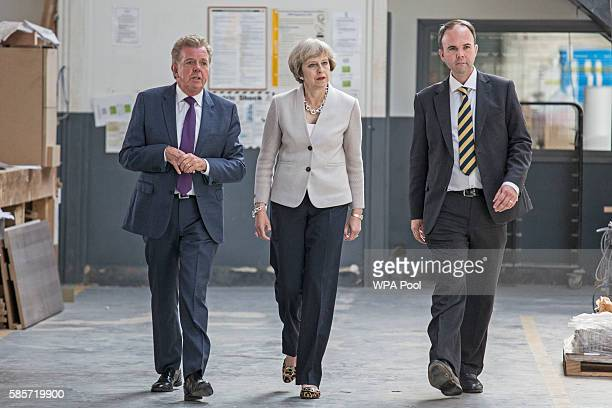 British Prime Minister Theresa May walks with Martek Managing Director Derek Galloway and Croydon Central MP Gavin Barwell during a visit to Martinek...